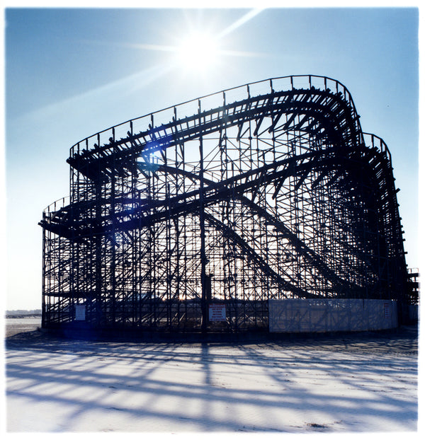 A rollercoaster structure throwing a shadow across the beach with the sun in a blue sky.