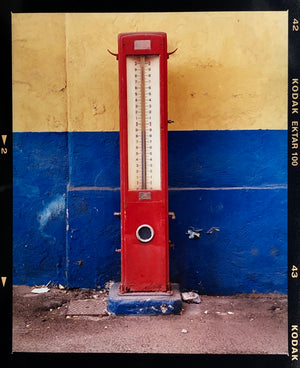 A red retro tyre pump against a yellow and blue painted wall, in the Porta Genova area of Milan.