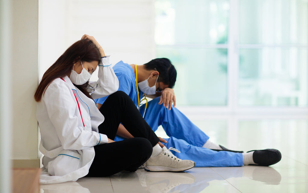 male female nurses tired exhausted sitting masks