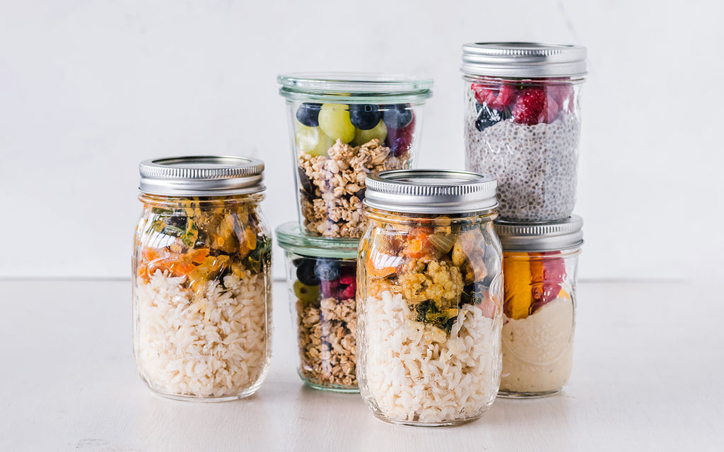 six mason jars filled with healthy foods for a weeks worth of meal preparation