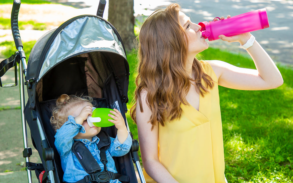 mother drinking from her hot pink hidrate spark 3 bluetooth smart water bottle while her child drinks from her sippy cup