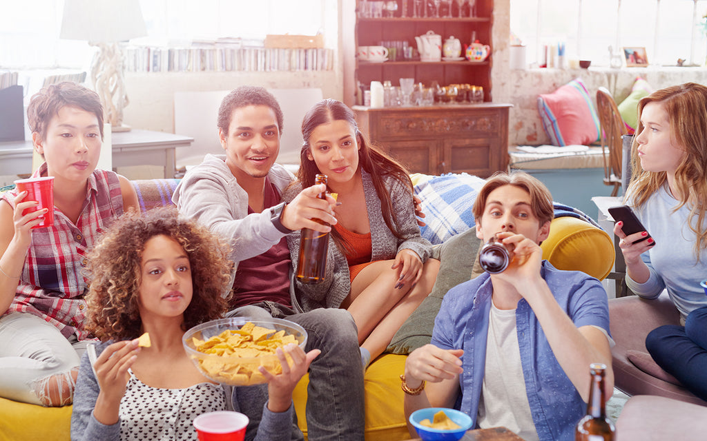 friends in an urban loft gathering around the tv watching a sporting event