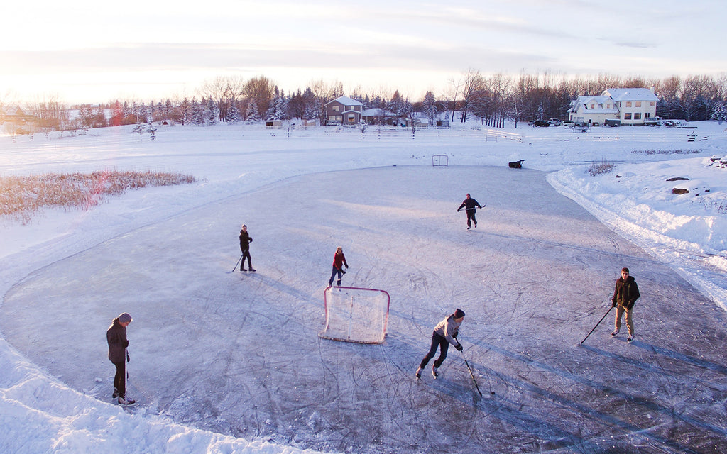 group of people ice skating on a frozen lake playing hockey