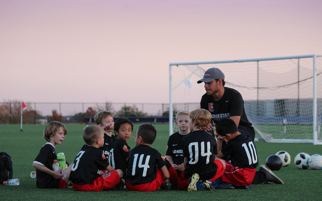 a youth soccer team sits down to rest in their after practice huddle