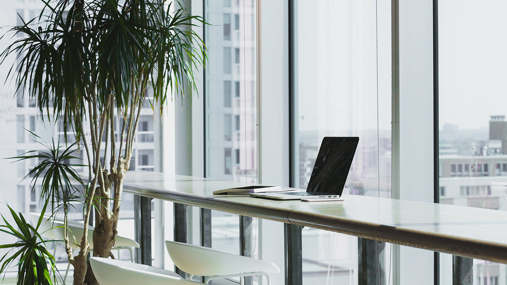 work station located next to floor to ceiling windows for a beautiful view of the city