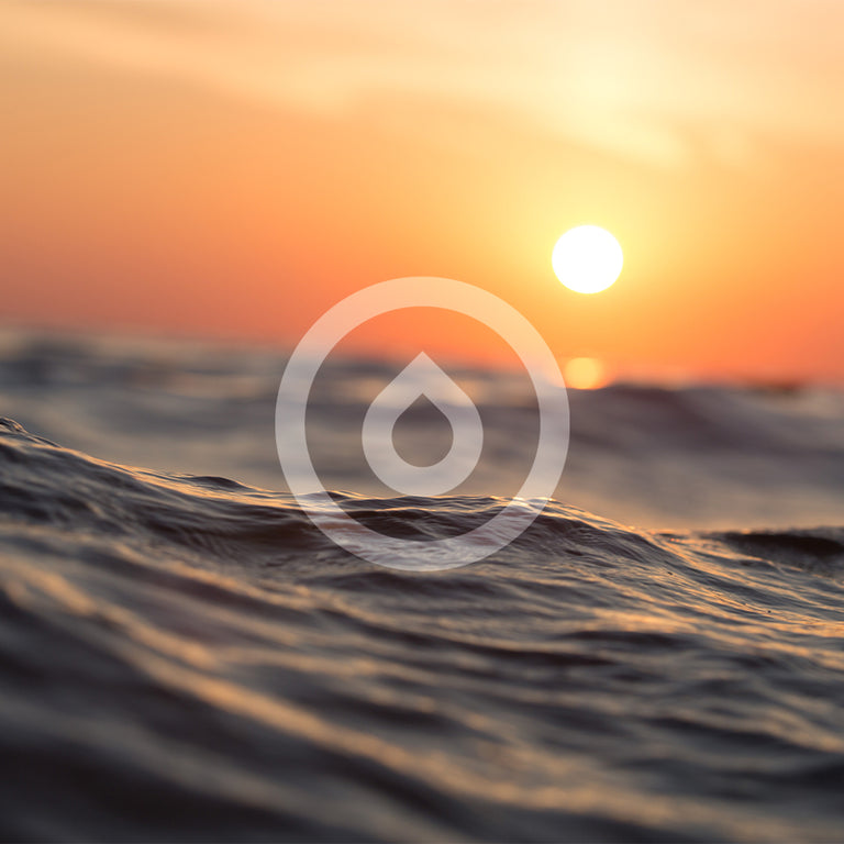 transparent white hidratespark water drop logo on top of a beautiful sunset