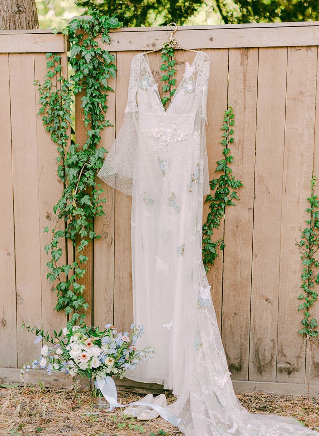 Chrysalis Wedding Dress on Hanger in Garden Setting