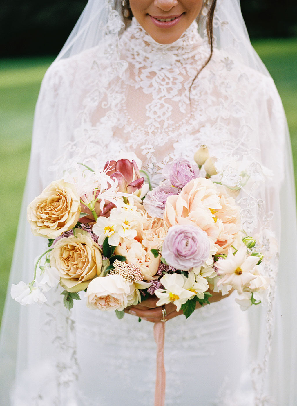 Bride wearing Grace Lace Wedding Dress by Clare Pettibone hold floral boquet
