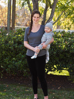 Woman holding a baby and wearing a gray relaxed fit breastfeeding Tee shirt.