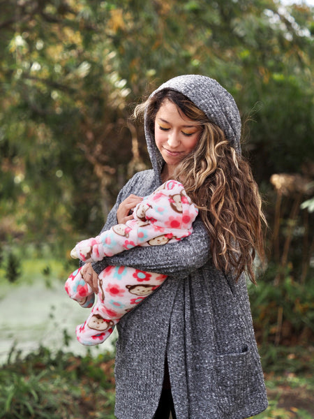 Woman holding a baby and wearing a hooded gray nursing sweater with pockets.