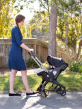 Woman pushing a baby in a stroller wearing a blue wrap nursing dress.