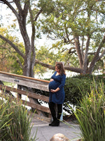 Pregant woman wearing a blue maternity wrap dress.