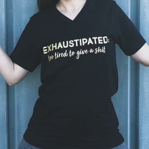 black shirt with gold design that says 'exhaustipated; too tired to give a shit'