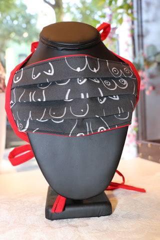 A face mask is on a black necklace display form. The facemask has a black background with white boob line sketches in a variety of shapes and sizes, it has red lining.