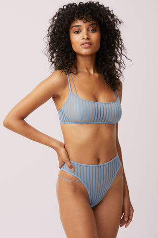 size XS light skinned black model with natural hair to her shoulders stands with right arm on her hip. with hip popped to one side. wearing a denim blue color opaque striped boat neck bralette with double strap detail and matching highwaisted panty