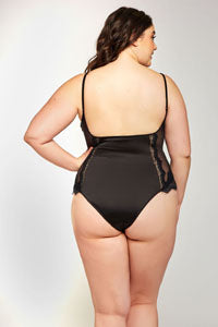 A brown haired model stands with her back to the camera and her left hand on her hip. She is wearing a black satin teddy with a scoop back that rests at the mid back. The bottom of the teddy is a cheeky cut that slightly shows off the bum.