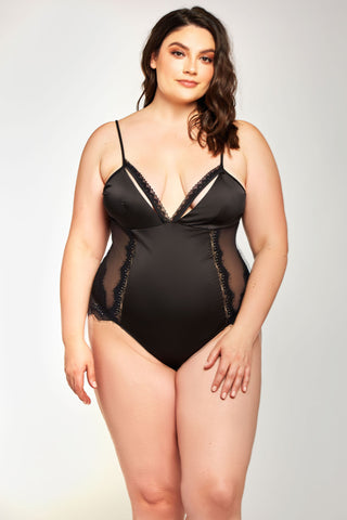 a brown haired white model stands with her left hand resting on her upper thigh. She is wearing a black teddy with a stain panel (not see through) down the mid section. It is adorned with a lace panel up each side and delicate peek-a-boo trim on the cups. She is wearing a size extra large