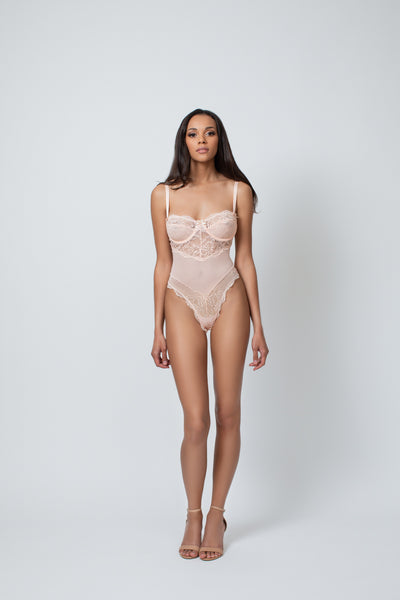 a tan model stands facing the camera with her hands resting at her sides, this is the same image as the one before except it shows the length of her long legs.. She is wearing a Kilo Brava peach colored bodysuit teddy that is a couple shades lighter than her skintone. The teddy has underwire, lace cups, and a mesh panel down the torso.. The model is wearing a size small