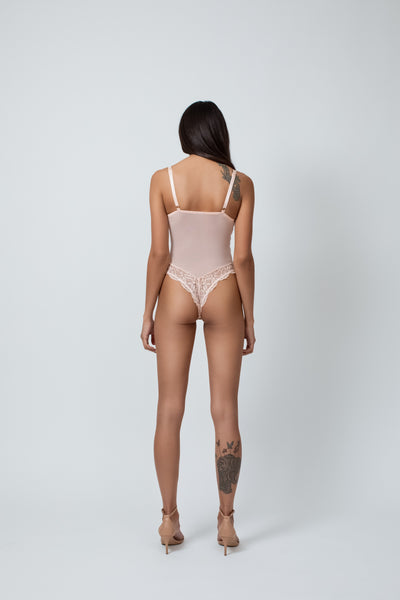 a tan model stands facing away from the camera with her hands resting at her sides, she has a tattoo on her right ankle/calf. She is wearing a Kilo Brava peach colored bodysuit teddy that is a couple shades lighter than her skintone. The teddy has mesh bodice, adjustable straps, and lacy tenga cut bottom that shows off her bum cheeks.