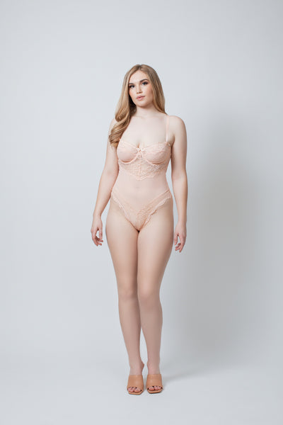 a pale model stands facing the camera with her hands resting at her sides. She is wearing a Kilo Brava peach colored bodysuit teddy that is a similar color to her porcelain skin tone. The teddy has underwire, lace cups, and a mesh panel down the torso.. The model is wearing a size XL