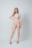 a pale model stands facing the camera with her right hand on her hip. She is wearing a Kilo Brava peach colored bodysuit teddy that is a similar color to her porcelain skin tone. The teddy has underwire, lace cups, and a mesh panel down the torso.The model is wearing a size XL