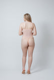 a pale model stands facing away from the camera with her right hand on her hip. She is wearing a Kilo Brava peach colored bodysuit teddy that is a similar color to her porcelain skin tone.  The teddy has mesh bodice, adjustable straps, and lacy tenga cut bottom that shows off her bum cheeks