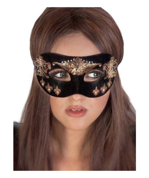 white woman wears a black mask flocked with velvet texture and adorned with gold rhinestones and fluer de lis detailing