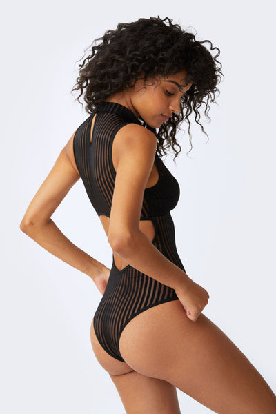size 0 light skinned black model stands with a profile view with both arms on her hips. wearing a black opaque striped teddy with highneck. this image shows the lower back cut out and cheeky bum cut of the teddy