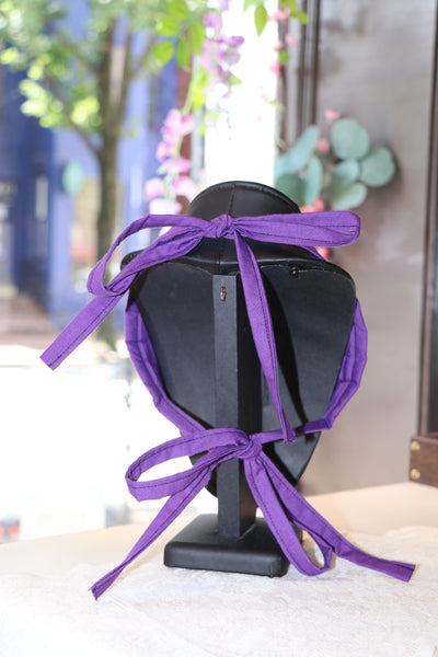 The back of a facemask on a jewelry display form, shows the purple ties which tie at the  top of the head and at the bottom of the head by the chin.