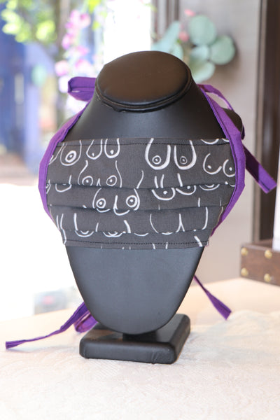 A face mask is on a black necklace display form. The facemask has a black background with white boob line sketches in a variety of shapes and sizes, it has purple lining.