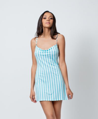 brown model wearing bamboo fabric mini slip that goes to high thigh. pattern is vertical blue and white stripes with thin straps