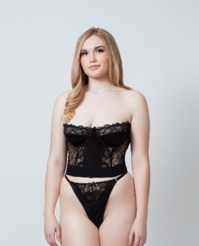 a pale model wearing size XL stands facing the camera. She is wearing a Kilo Brava strapless satin and lace bustier in black. She wears a matching high cut g-string panty with thing strappy waist band