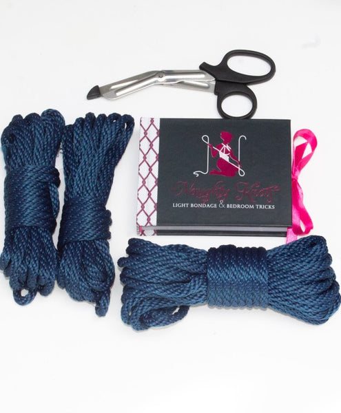 flay lay of a beginner bondage set with two hanks of 15ft rope, 1 hank of matching 30ft rope in navy blue. naughty knots instructional book, and safety scissors.