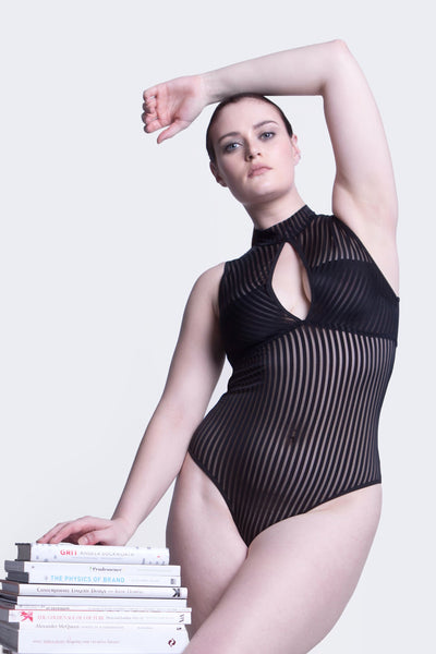 size 12 white model stands with left arm draped over head and legs crossed with hips popped to one side. wearing a black opaque striped teddy with a cut out at the bust and a highneck cut neckline