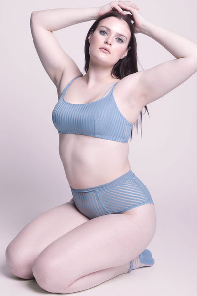size LG white model with brown hair to mid back kneels with back arched & hands on her head. wearing a denim blue color opaque striped boat neck bralette with double strap detail and matching highwaisted panty