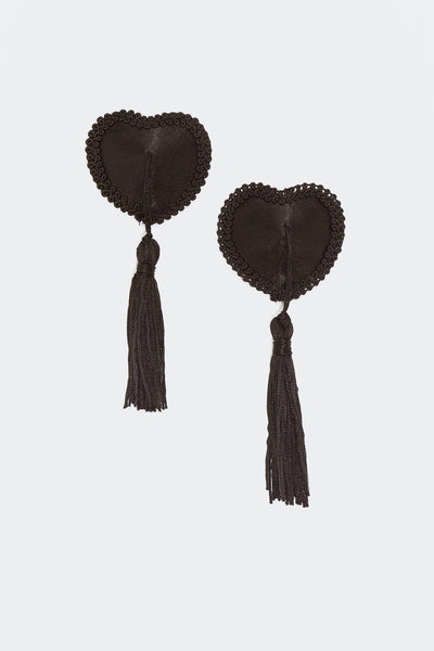 Black satin pasties in a heart shape with black tassels hanging from the middle. adorned with swirled ribbon on the outer edge