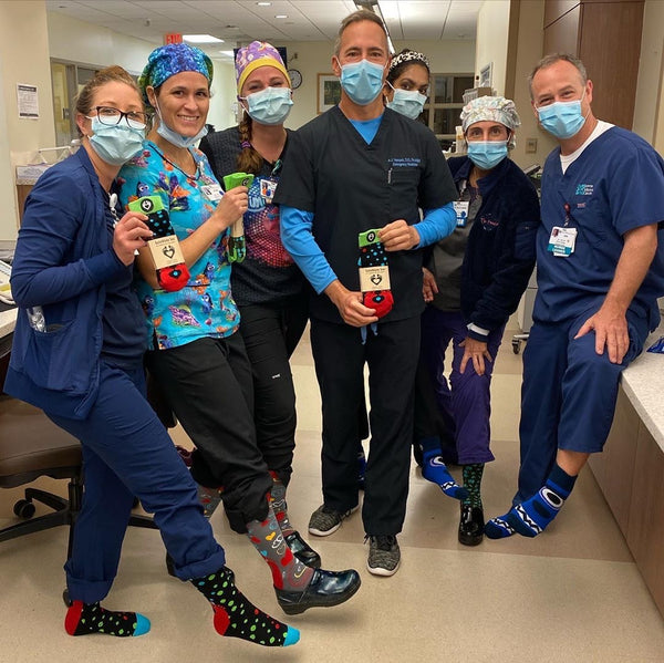 Health care workers dressed in scrubs wearing SoleMate Sox