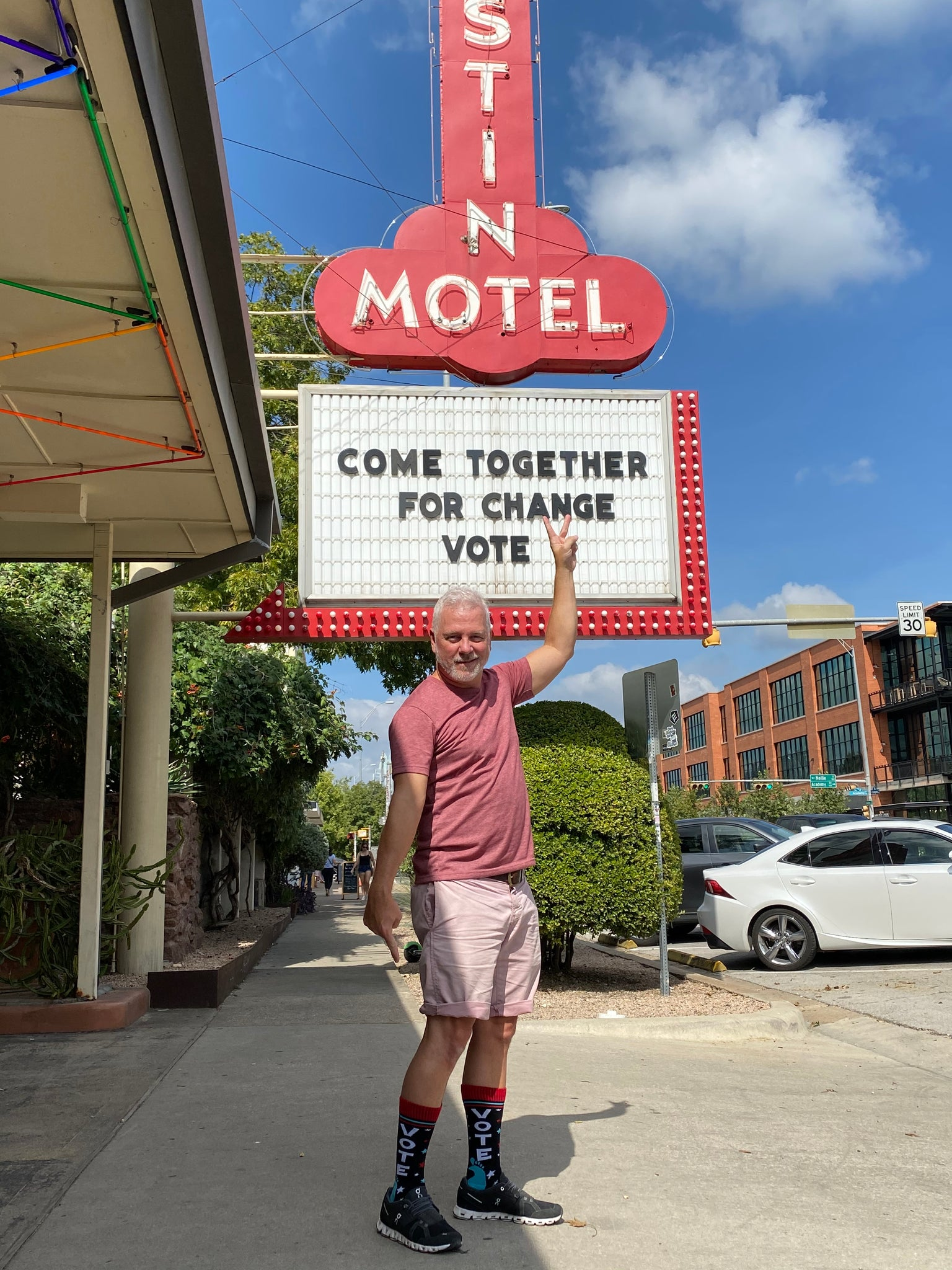 Middle-aged white haired man standing in front of Austin Motel in Austin, Texas modeling and wearing SoleMate Sox Midnight VOTE socks