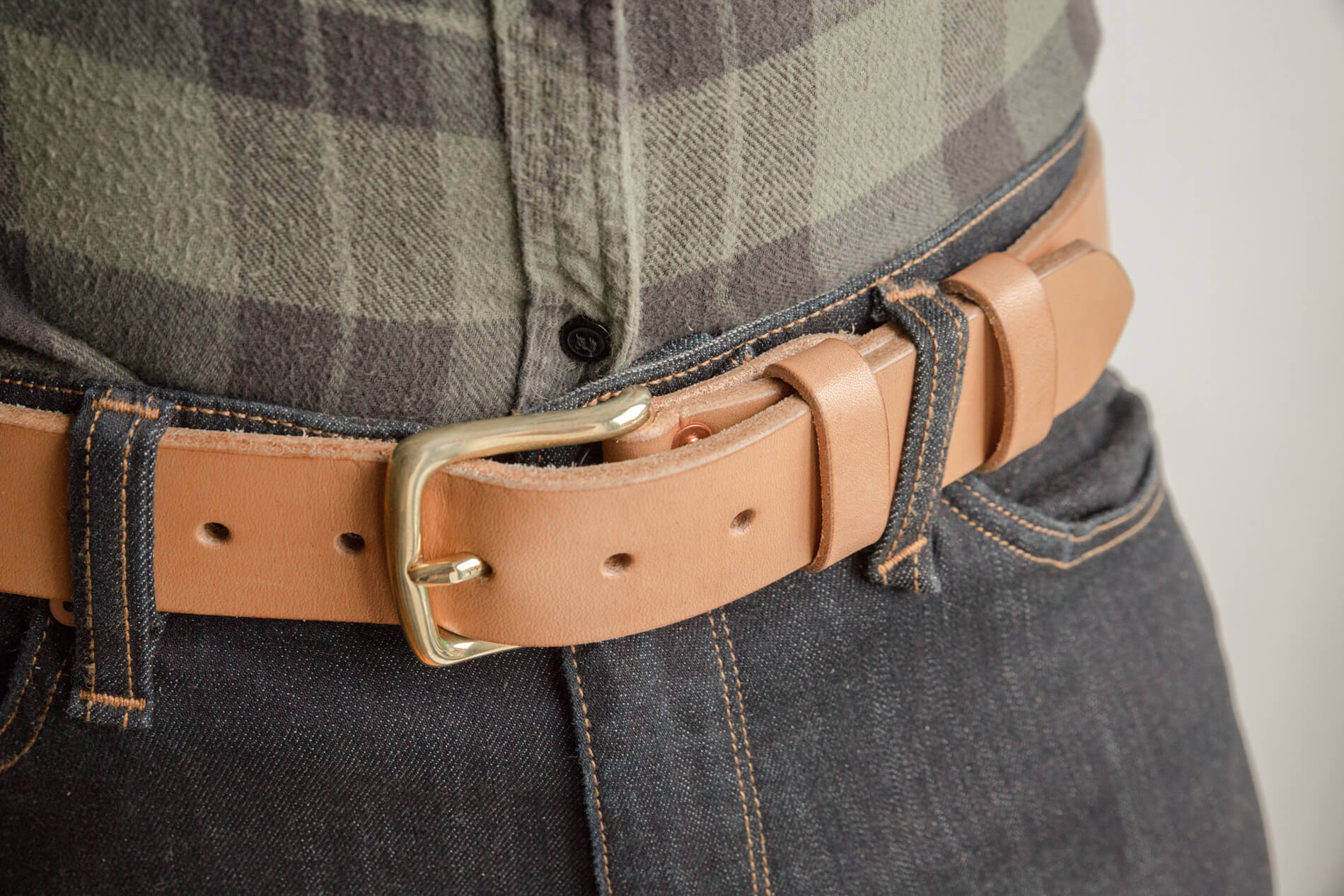 Handmade leather belt on blue denim jeans
