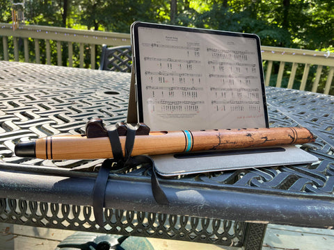 N cherry Native American Flute sitting on a table next to an ipad showing sheet music for the native american flute