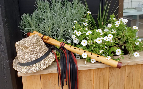 A native american flute lying next to a fedora had in a planter box