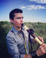 Timothy J.P. Gomez playing his Native American Flute in a field posing for the upcoming Native American flute workshop with Jonny Lipford