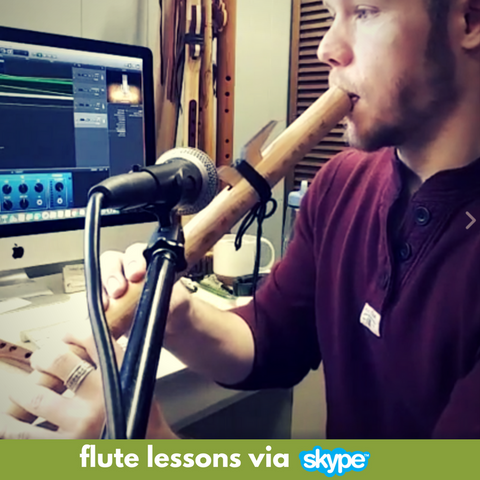 Jonny Lipford playing flute into a microphone in front of a computer while giving a Native American flute lesson via skype