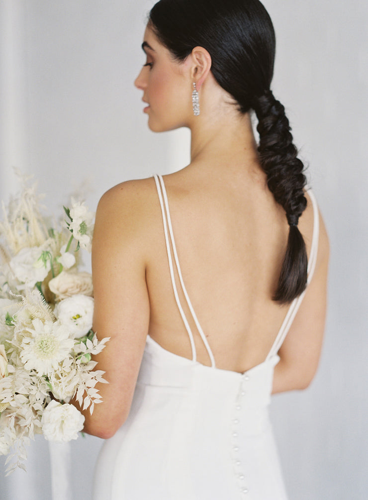 Simple wedding dress with V-neck and fitted silhouette and a gorgeous front split detail.