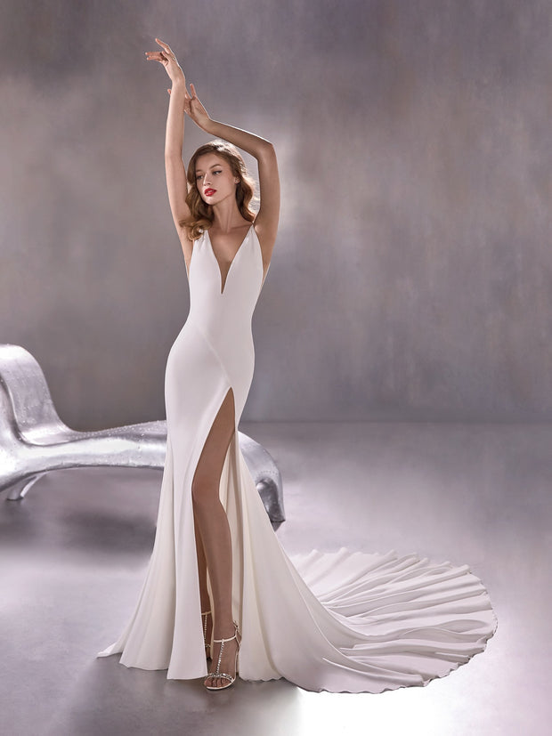 A crepe mermaid wedding dress with a high slit skirt and a bold, plunge neckline and back.