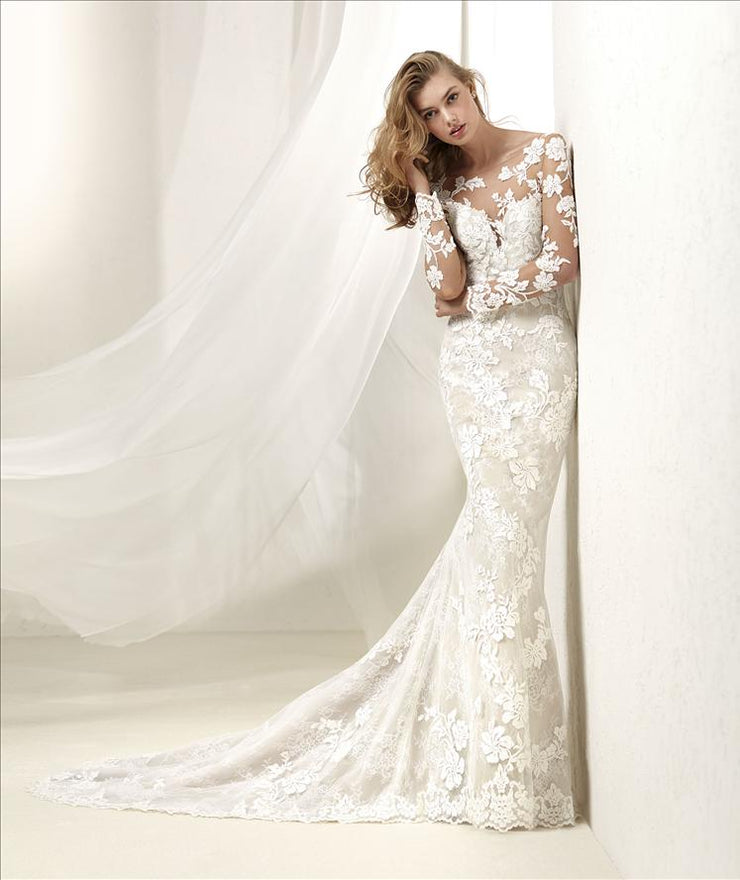 Stunning wedding dress with a tattoo effect in long sleeves and round plunging neckline.