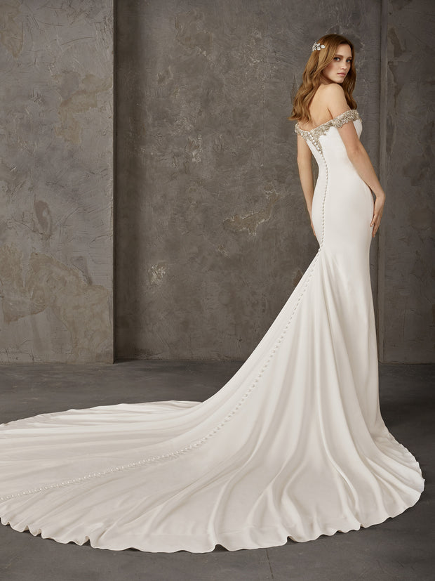 Pronovias Newton is a crepe mermaid dress with a long train, plunging v and off-the-shoulder straps.