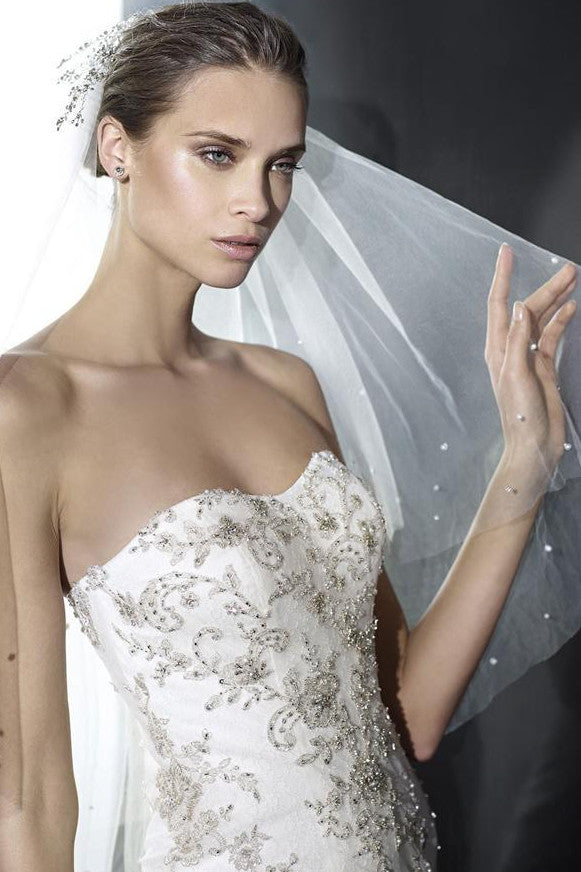 A strapless mermaid wedding dress with embroidery on the bodice leading into the train.