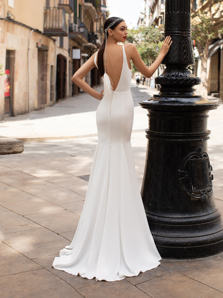 Pronovias PWD 04 is a mermaid dress in all-over crepe with a deep plunge V-neck and an open back.