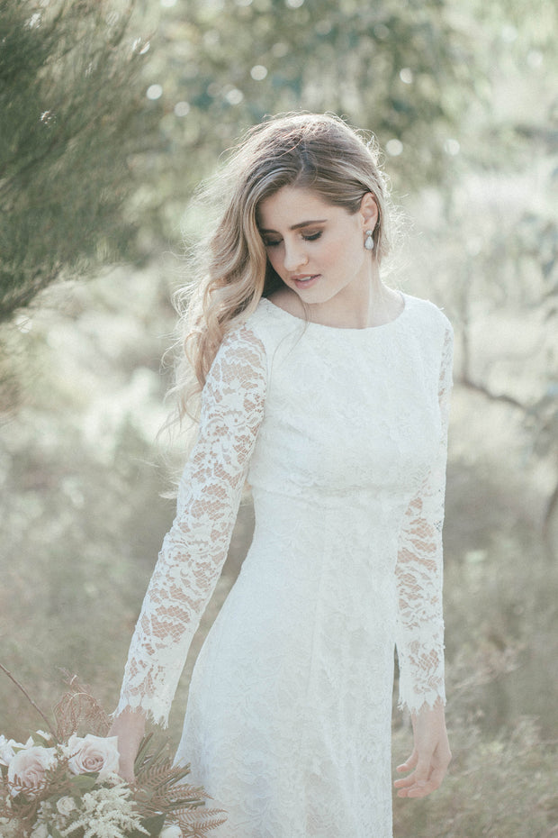 Lace wedding dress with long sleeves, a classic neckline and a fitted silhouette.